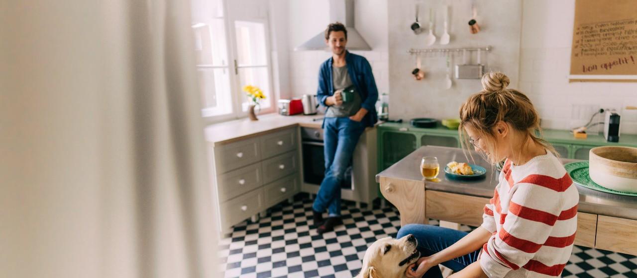 Junge sitzt in einer Hängematte im Garten vor einem Haus.